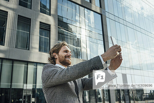 Smiling male professional taking selfie against office building at downtown district