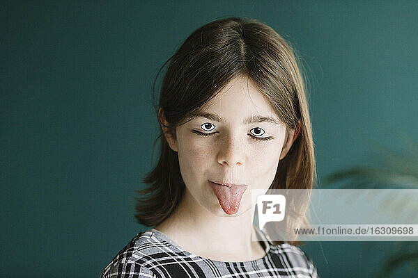 Close-up of girl with googly eyes and make-up sticking out tongue against wall at home