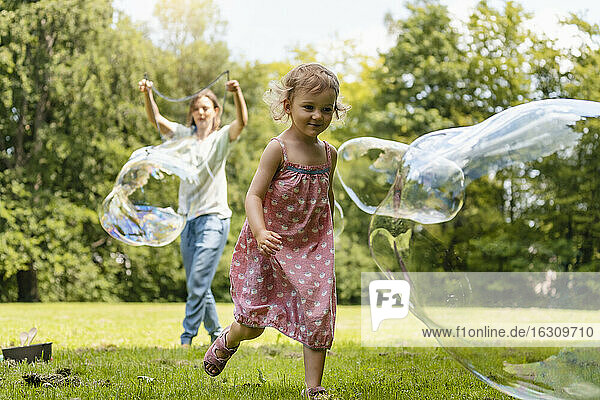 Baby girl running after bubble with mother standing in background at park