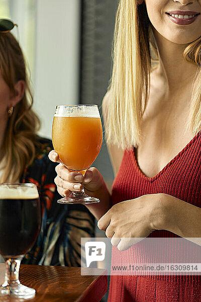 Frau hält ein Glas Craft Beer in einer Kneipe Frau hält ein Glas Craft Beer in einer Kneipe