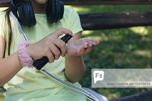 Girl using hand sanitizer while sitting on bench in park
