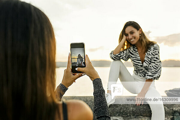 Woman taking photo of friend sitting on retaining wall at promenade