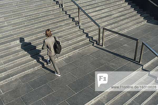 Businessman with bag moving up on staircase in downtown during sunny day