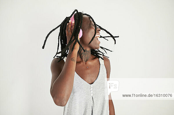 Fröhliche Frau mit Kopfhörern hört Musik vor weißem Hintergrund Fröhliche Frau mit Kopfhörern hört Musik vor weißem Hintergrund