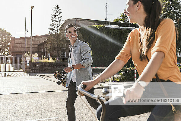 Cheerful young man looking at girlfriend riding bicycle on street in city during sunny day