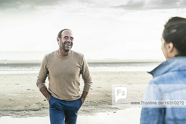 Cheerful man with hands in pockets looking at woman while standing against sea