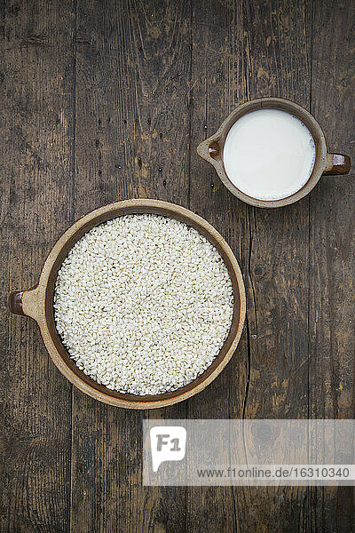 Ingredients of rice pudding on wooden table  studio shot