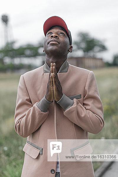 Junger Mann betet mit religiösem Glauben im Freien stehend