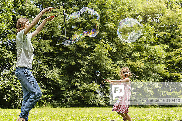 Happy daughter exploding bubble with mother at park
