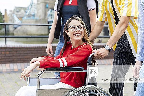 Lächelnde junge Frau im Rollstuhl genießt das Wochenende mit Freunden in der Stadt