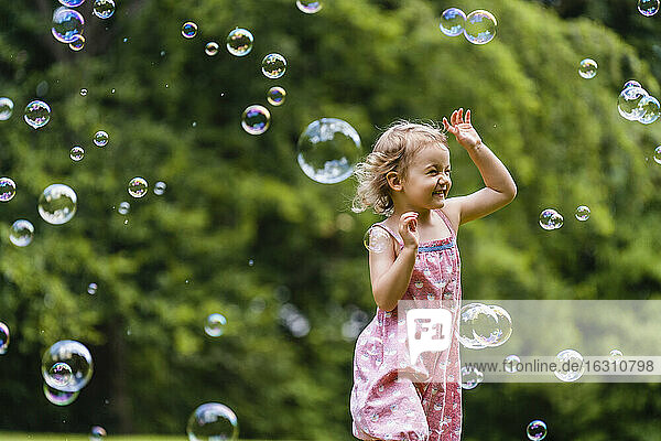 Cheerful girl running amidst bubbles at park