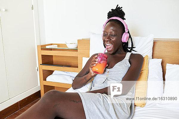 Junge Frau trinkt Saft und entspannt sich auf dem Bett zu Hause Junge Frau trinkt Saft und entspannt sich auf dem Bett zu Hause