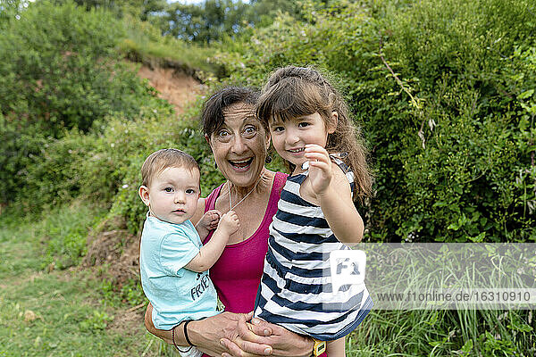 Cheerful grandmother carrying granddaughters in field