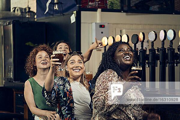 Aufgeregte Freundinnen  die in einer Kneipe am Tresen sitzen und fernsehen Aufgeregte Freundinnen, die in einer Kneipe am Tresen sitzen und fernsehen