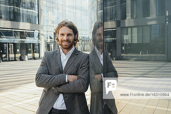 Handsome businessman standing with arms crossed by reflection on office building in financial district