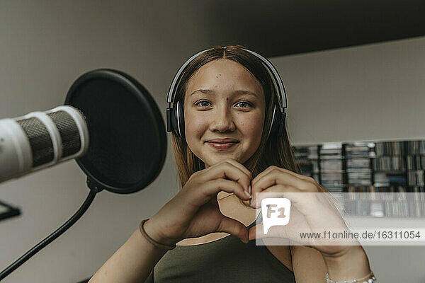 Close-up of smiling teenage girl making heart shape while singing in recording studio