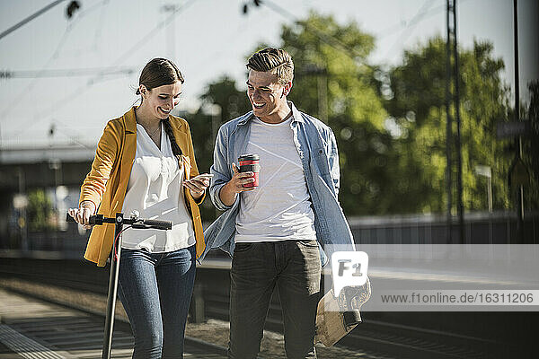 Young woman showing smart phone to male friend while walking at railroad station