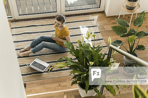 Woman wearing headphones holding drink while sitting with laptop on carpet at home