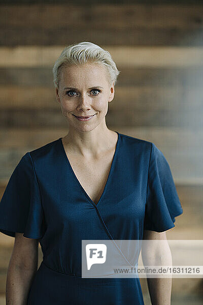 Confident businesswoman with short hair standing against wooden wall in office