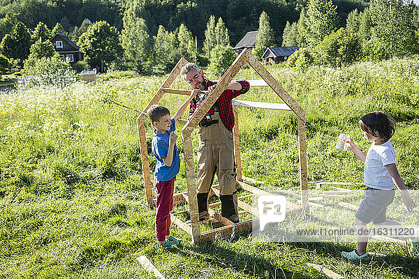 Children helping carpenter to build playhouse on sunny day
