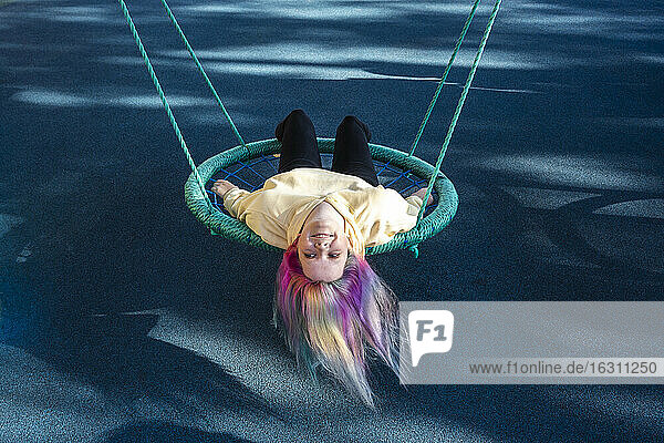 Young woman with dyed hair lying on swing