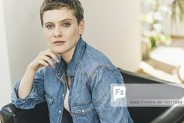 Confident beautiful woman with hand on chin sitting over armchair at home