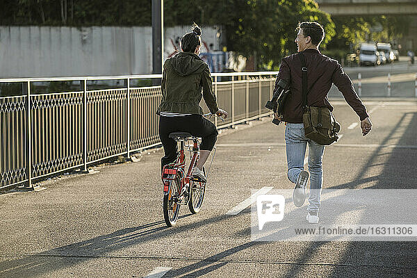 Young man carrying skateboard while running by girlfriend riding bicycle in city