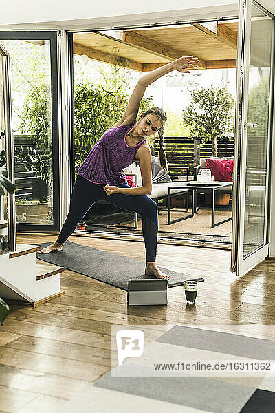 Young woman practicing yoga while looking in digital tablet at home