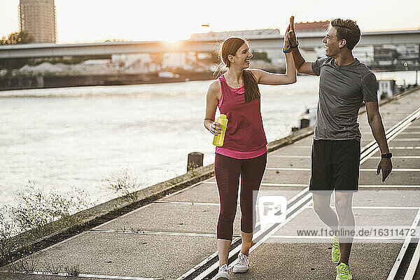 Smiling friends giving high-five while walking at harbor