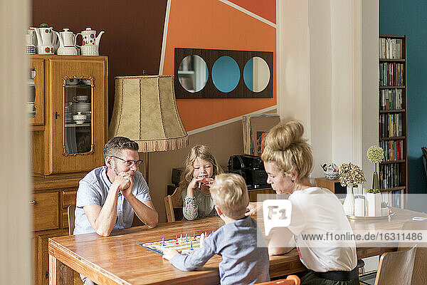 Family playing board game on dining table while sitting at home