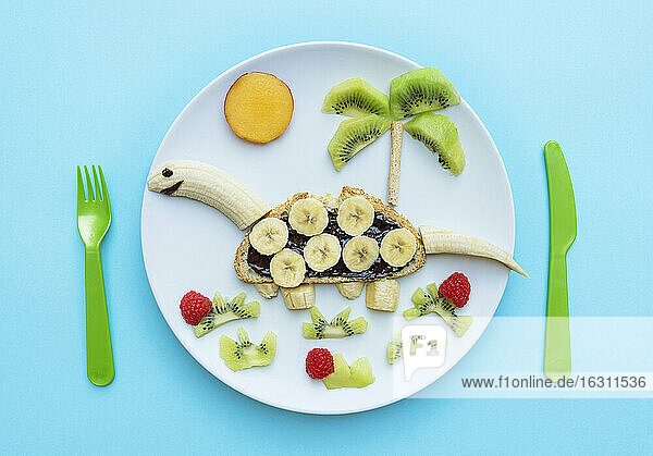 Breakfast with dinosaur shape made of banana  kiwi  bread  chocolate spread and berries on white plate on blue background