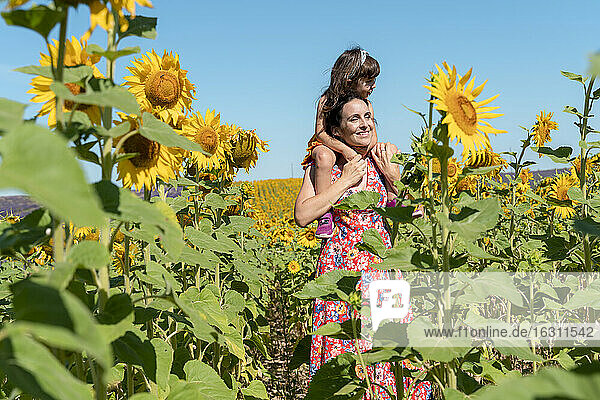 Smiling mother carrying daughter on shoulders in sunflower field during summer