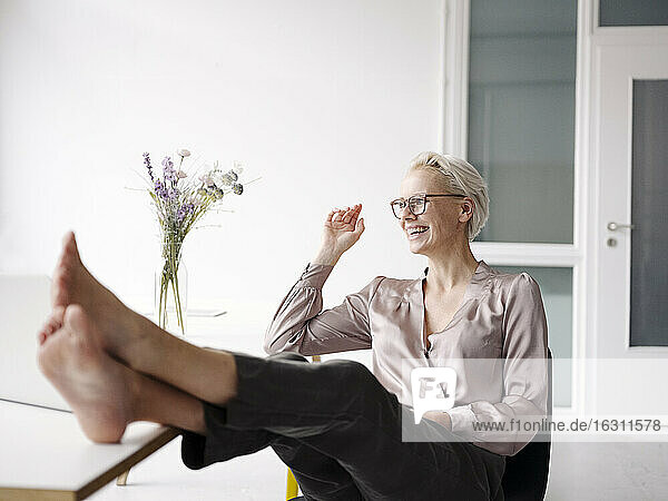 Smiling businesswoman with feet on desk relaxing in loft office