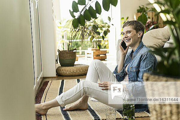 Cheerful woman talking over smart phone while sitting on carpet at home