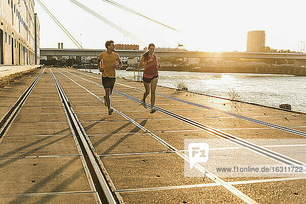 Male and female running at harbor during sunny day