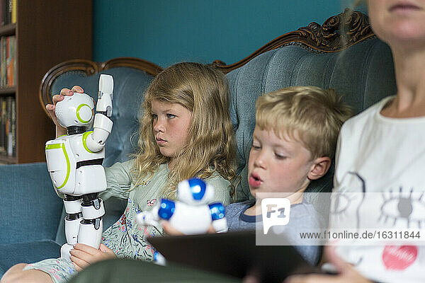 Blond girl playing with robot while sitting by sibling and mother at home