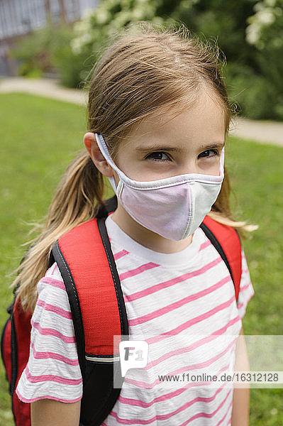 Schoolgirl (6-7) wearing flu mask
