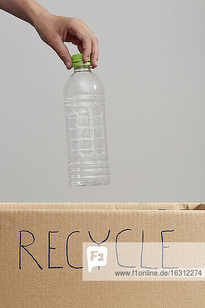 Close up of boys (8-9) hand putting plastic bottle into cardboard box