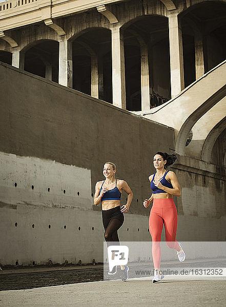 USA  Kalifornien  Los Angeles  Zwei sportliche Frauen joggen in städtischer Umgebung