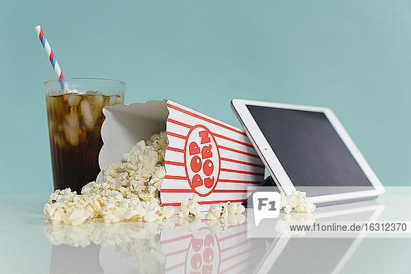 Studioaufnahme von Popcorn mit digitaler Tablette und Soda