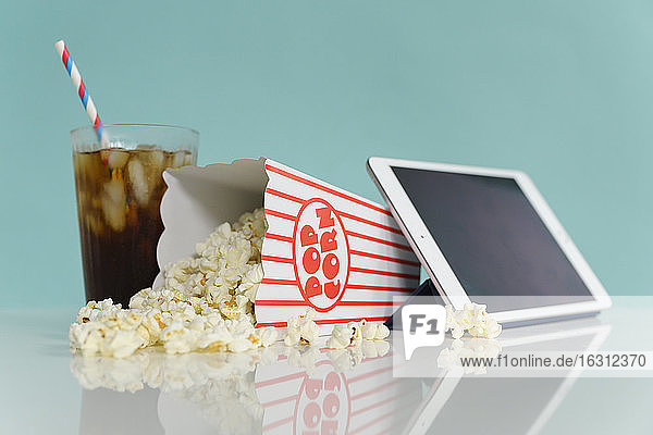 Studio shot of popcorn with digital tablet and soda