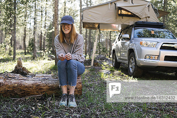 Portrait of smiling woman sitting on log on camping  car with tent in background  Wasatch Cache National Forest