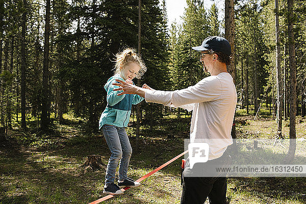 Father assisting daughter (2-3) walking on slackline in forest  Wasatch-Cache National Forest