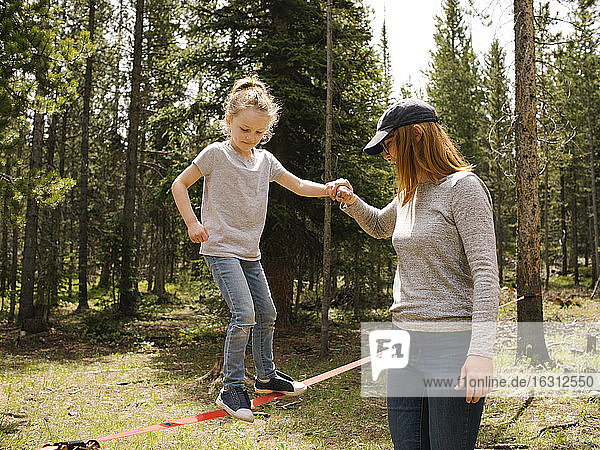Mother assisting daughter (6-7) walking on slackline in forest  Wasatch-Cache National Forest
