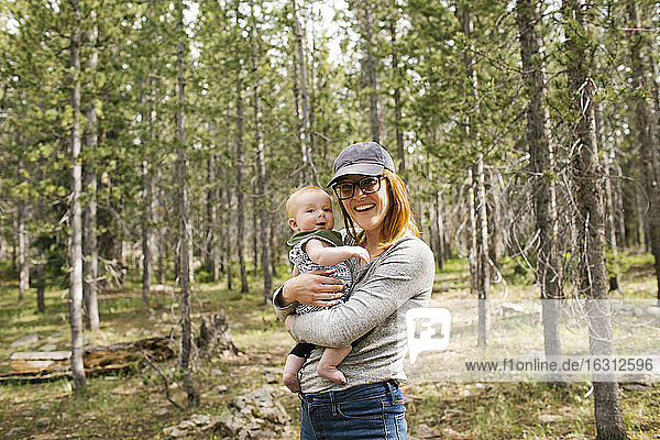 Portrait of smiling woman holding baby son (6-11 months) in forest  Wasatch Cache National Forest