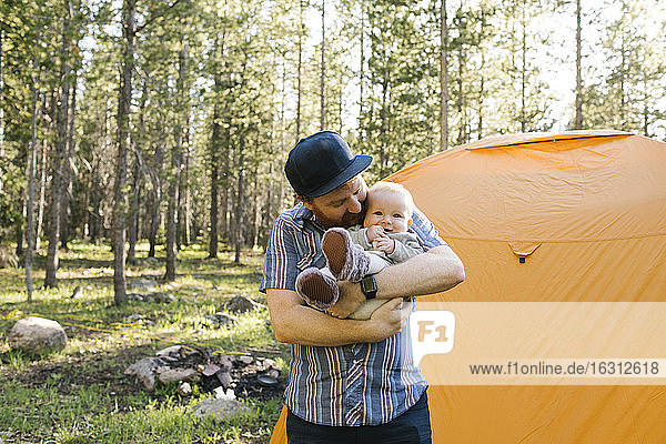 Father with baby boy(6-11 months) standing by tent in Uinta-Wasatch-Cache National Forest