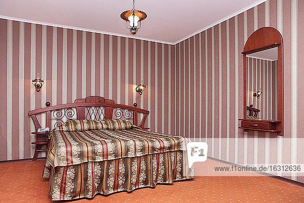 Ein Hotel mit Zimmern im altmodischen Retro-Stil  ein Schlafzimmer mit karierter Bettwäsche  gestreifter Tapete und Spiegel.