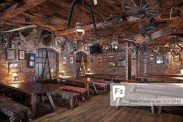 Ein Hotel mit altmodischen Zimmern im Retro-Stil und rustikalen Objekten  Café mit Tischen und Bänken.