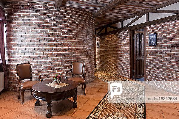 Ein Hotel mit altmodischen Zimmern im Retro-Stil und rustikalen Objekten  einer sichtbaren Steinwand und Tisch und Stühlen