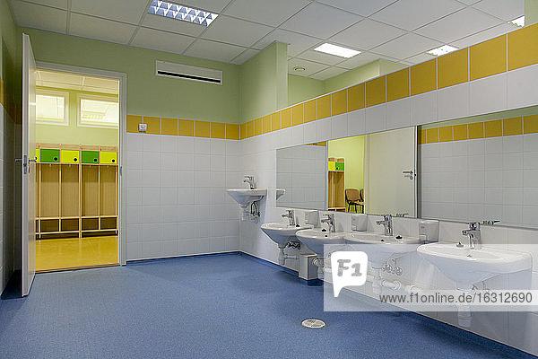 Schultoilette  moderner Stil mit gelber Farbe und blauem Bodenbelag